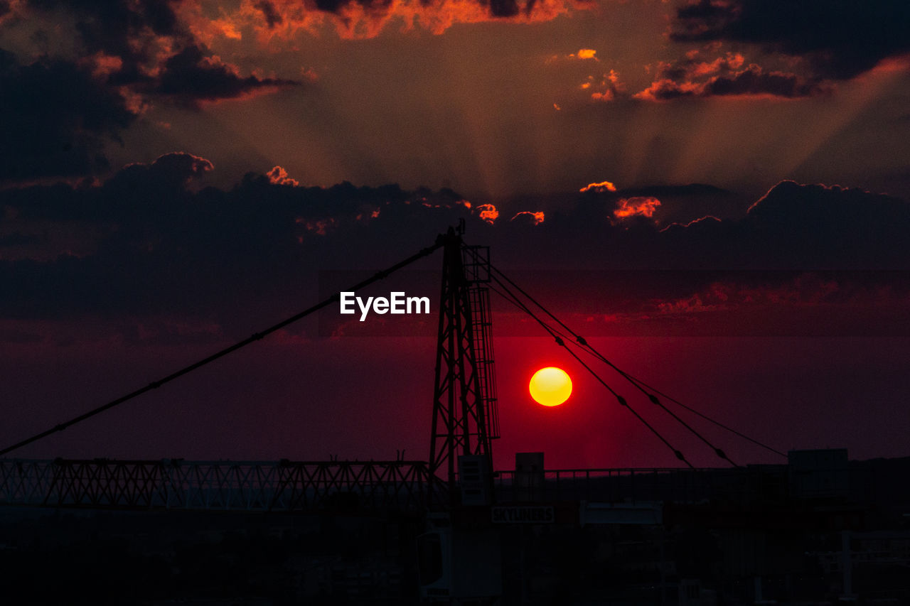sky, sunset, cloud - sky, orange color, architecture, silhouette, built structure, nature, no people, beauty in nature, low angle view, cable, outdoors, dusk, dramatic sky, construction industry, connection, machinery, electricity, industry, power supply, romantic sky, construction equipment
