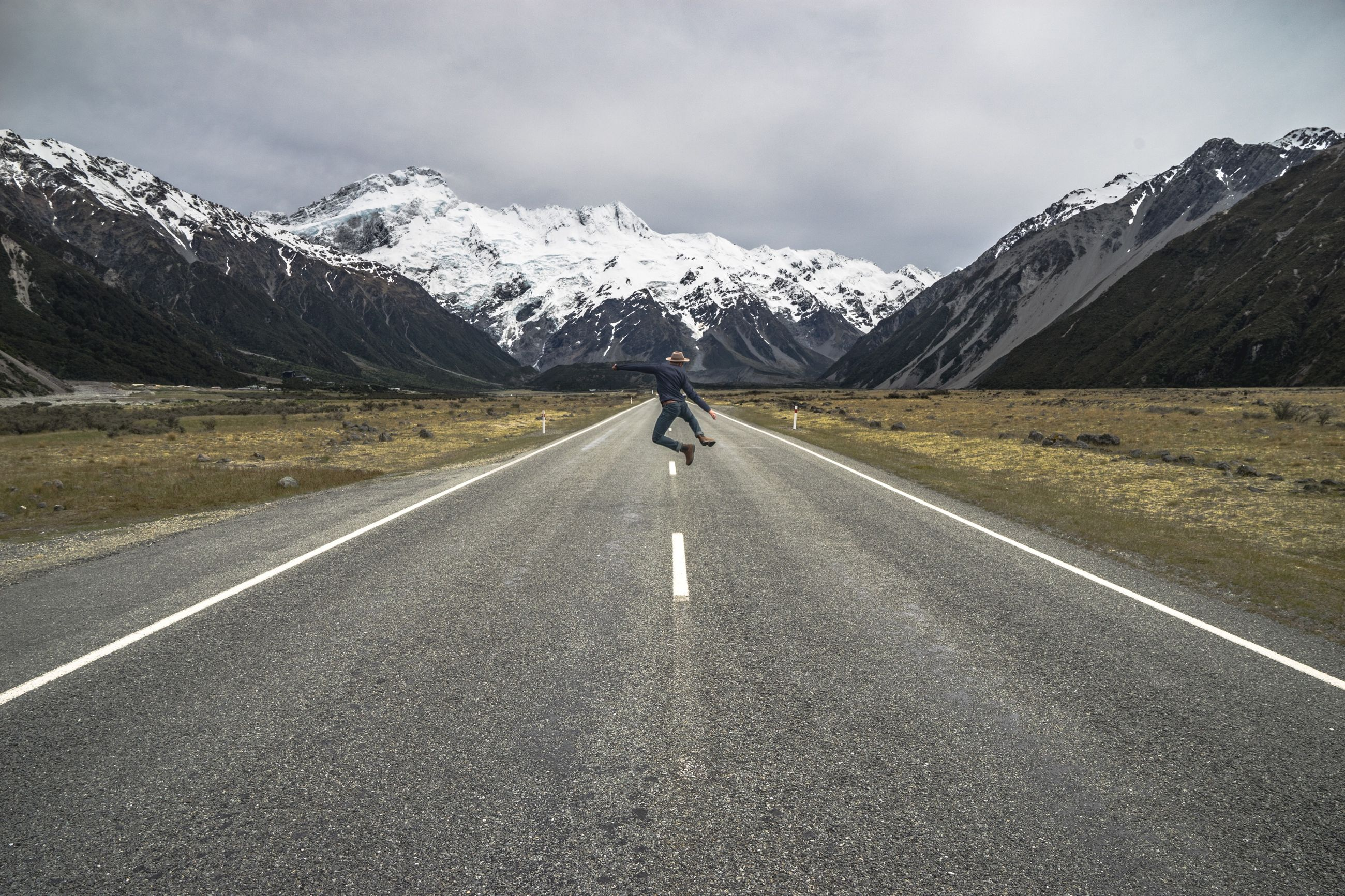Rear view of man jumping on road against snowcapped mountains