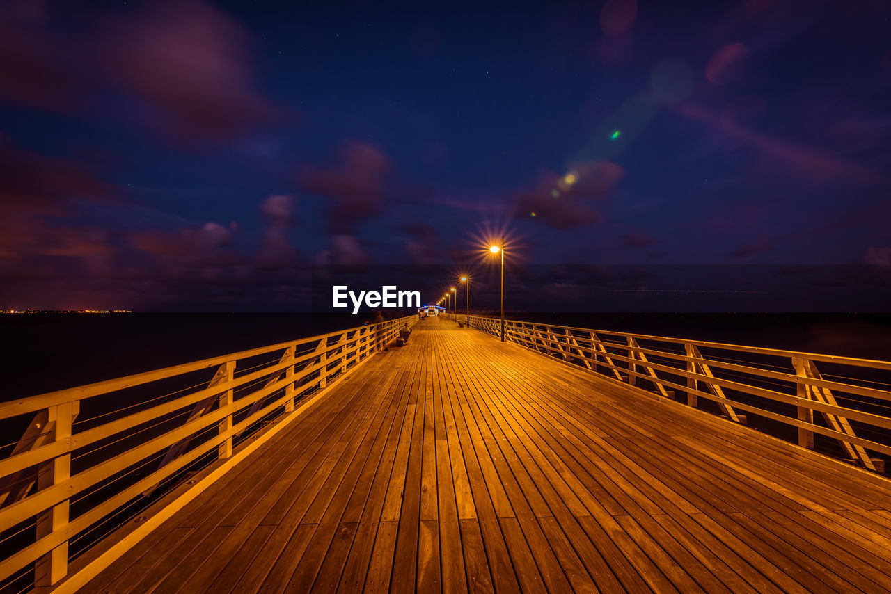 sky, illuminated, night, sea, the way forward, direction, cloud - sky, water, nature, railing, architecture, bridge, connection, transportation, built structure, beauty in nature, scenics - nature, sunset, wood - material, outdoors, no people, bridge - man made structure, diminishing perspective, horizon over water