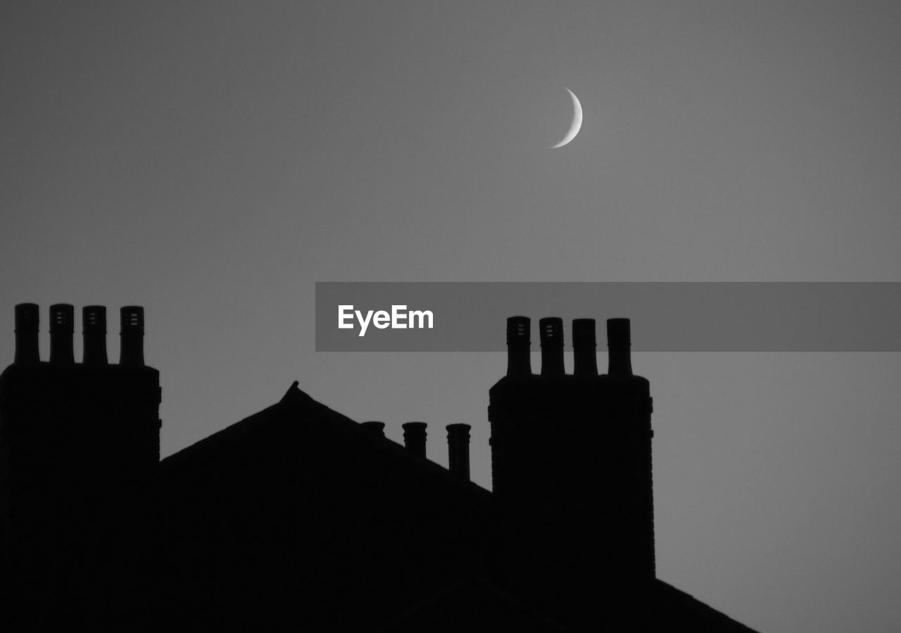 Crescent moon over building at night