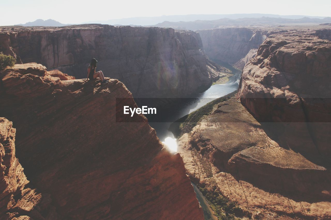 Scenic View Of Woman Sitting Atop Grand Canyon National Park