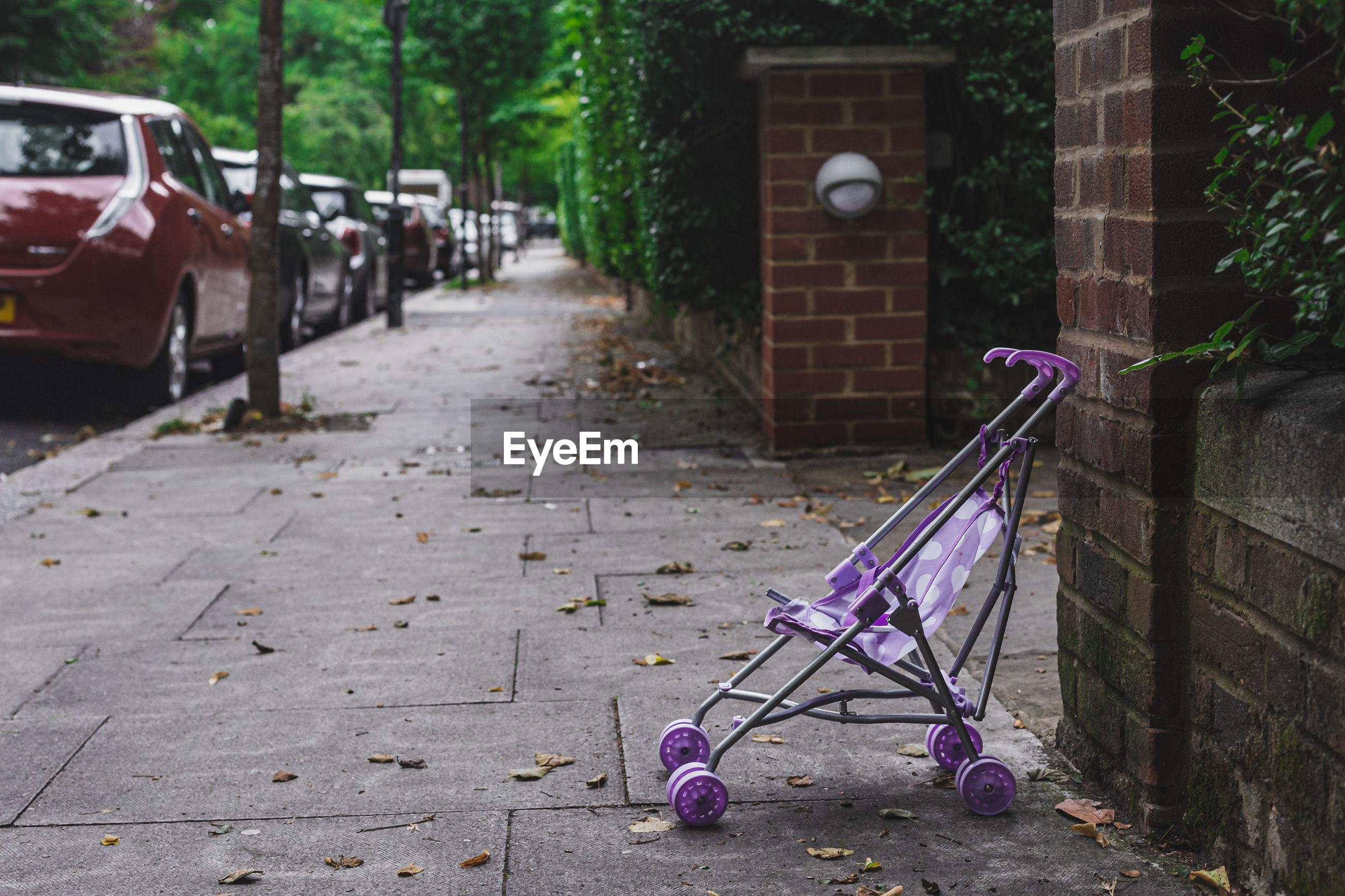 Empty footpath by street in city