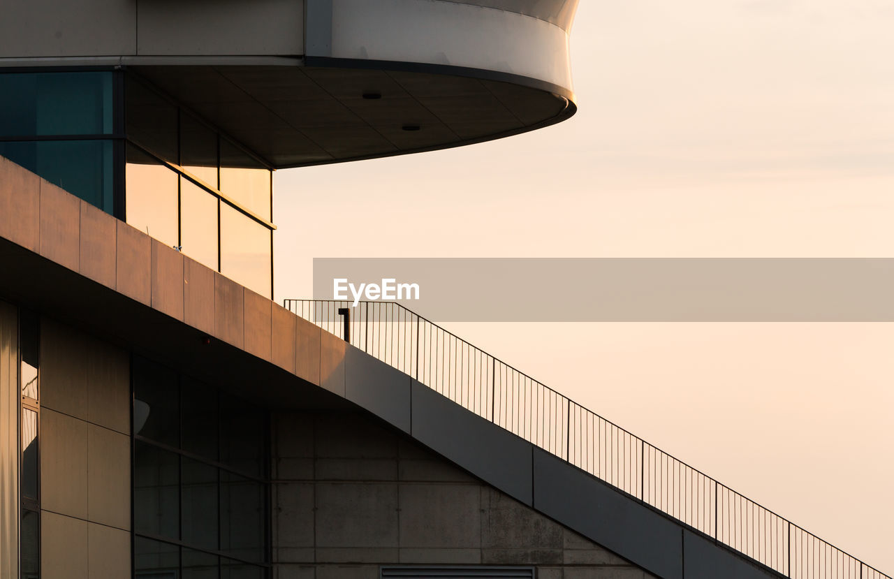architecture, built structure, building exterior, sunset, outdoors, bridge - man made structure, no people, low angle view, modern, sky, clear sky, day, city