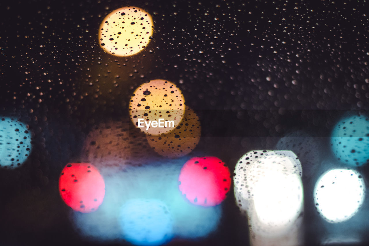 Defocused image of colorful lights seen through wet glass window at night