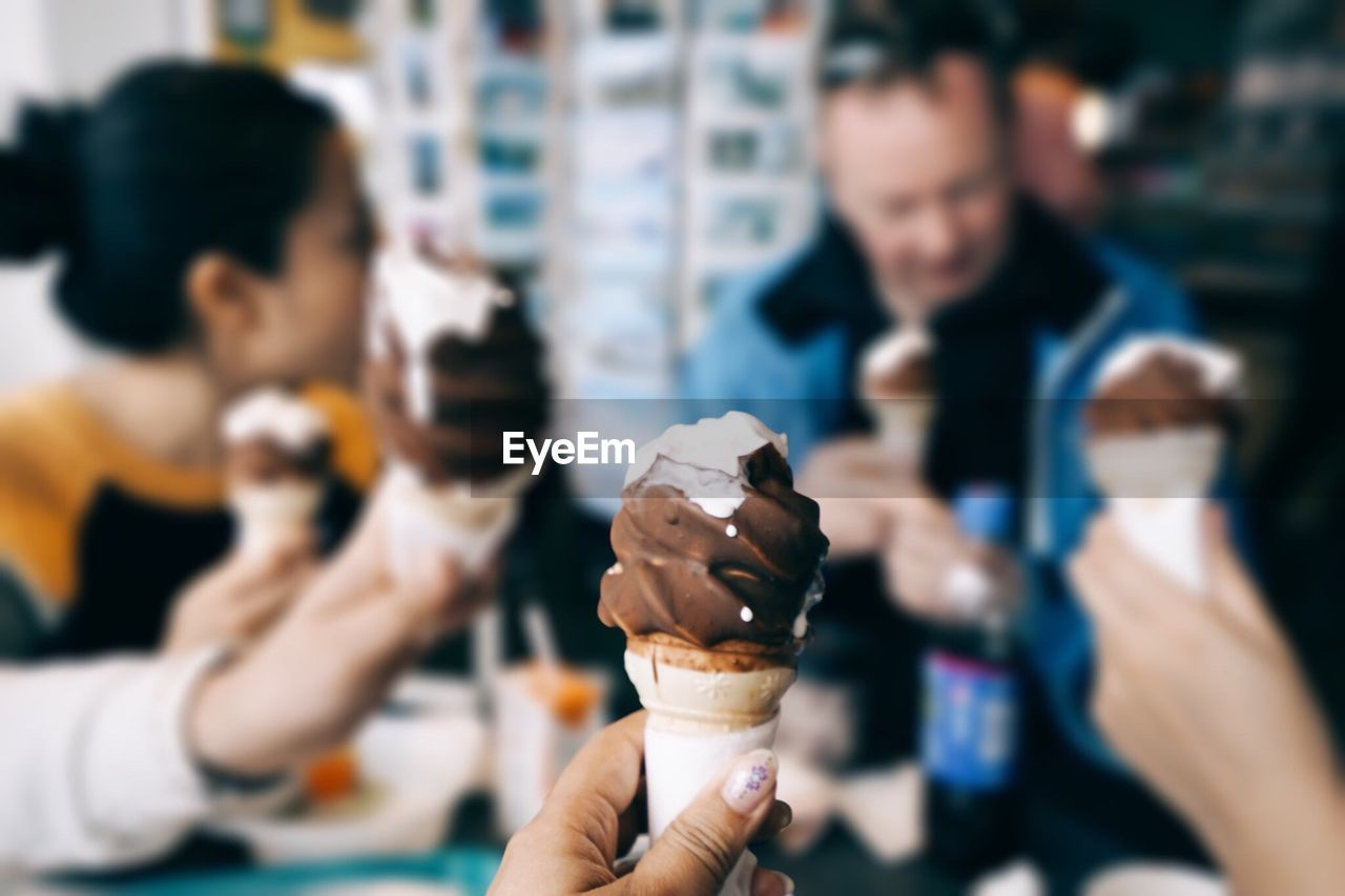 Cropped Image Of Woman Holding Ice Cream Cone At Restaurant