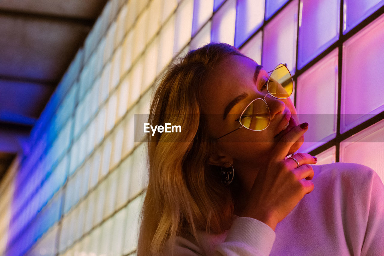 Young Woman In Sunglasses By Illuminated Wall