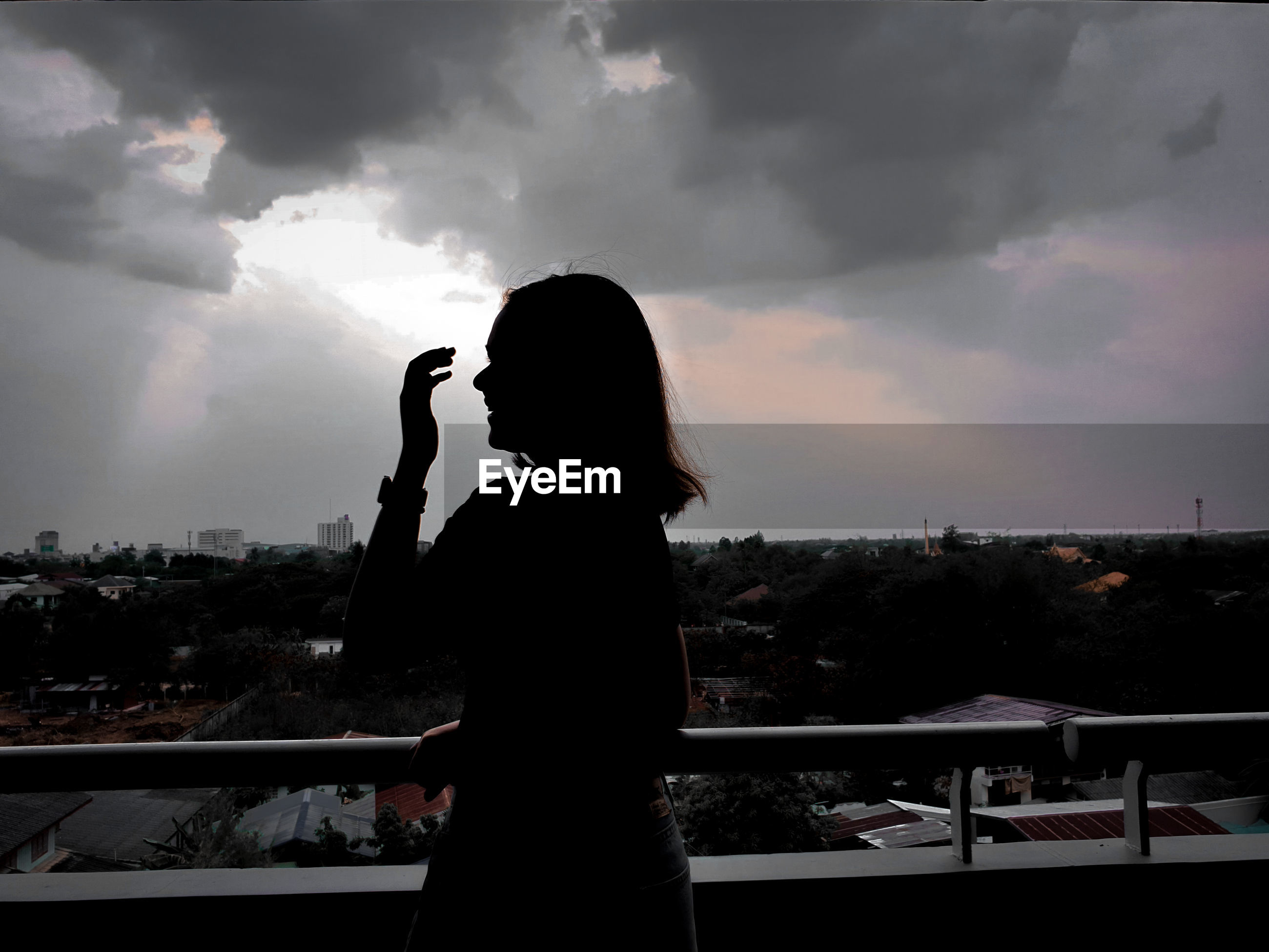 Side view of silhouette woman photographing cityscape against sky