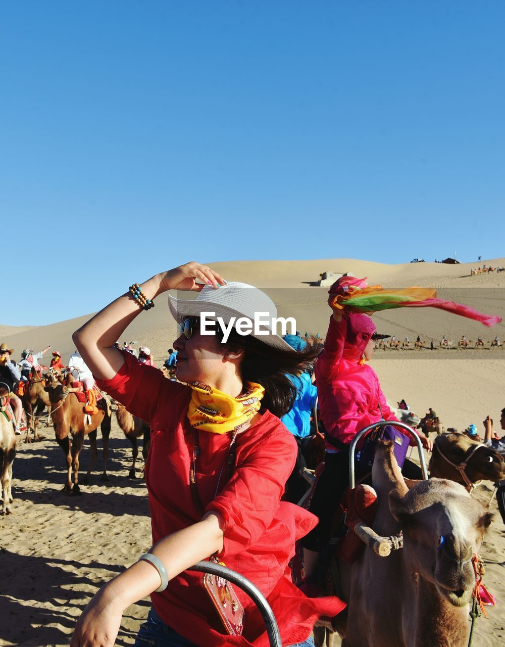 People at desert against clear blue sky during sunny day