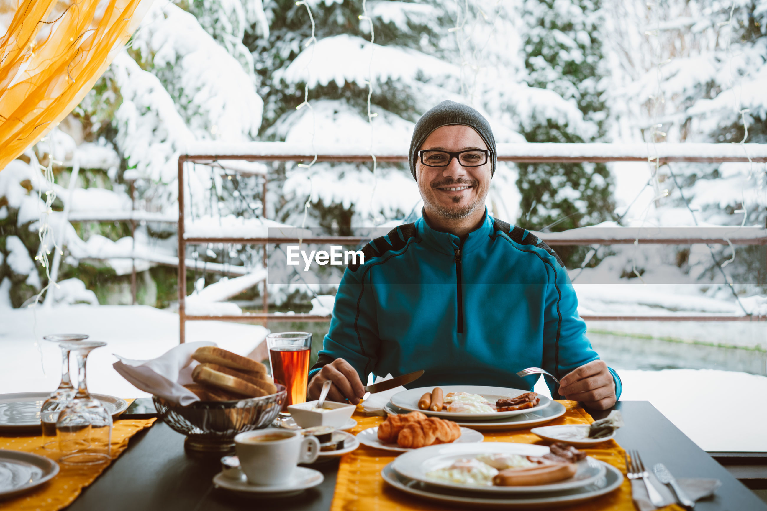 Portrait of smiling man with breakfast on table