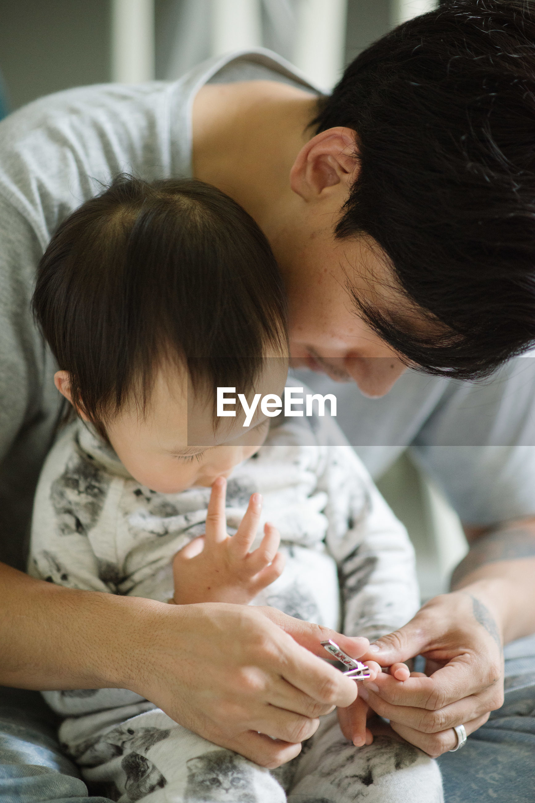 Close-up of father clipping baby's fingernails