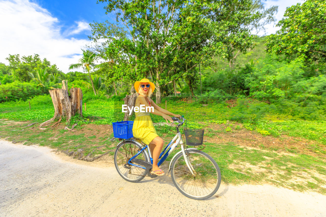 young adult, plant, transportation, one person, bicycle, tree, nature, full length, land, leisure activity, grass, women, land vehicle, day, adult, green color, real people, young women, lifestyles, field, fashion, riding, outdoors, hairstyle, beautiful woman