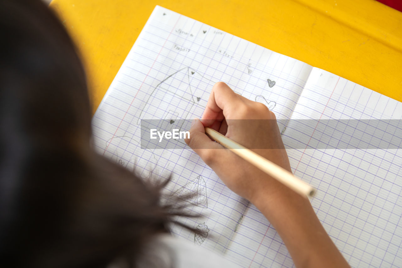 Girl drawing on book at table