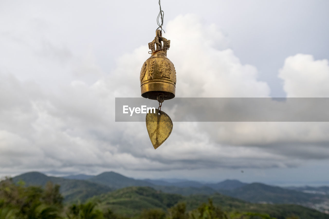 cloud - sky, sky, mountain, nature, no people, beauty in nature, scenics - nature, outdoors, hanging, day, focus on foreground, gold colored, bell, low angle view, tranquil scene, mountain range, religion, green color, tranquility