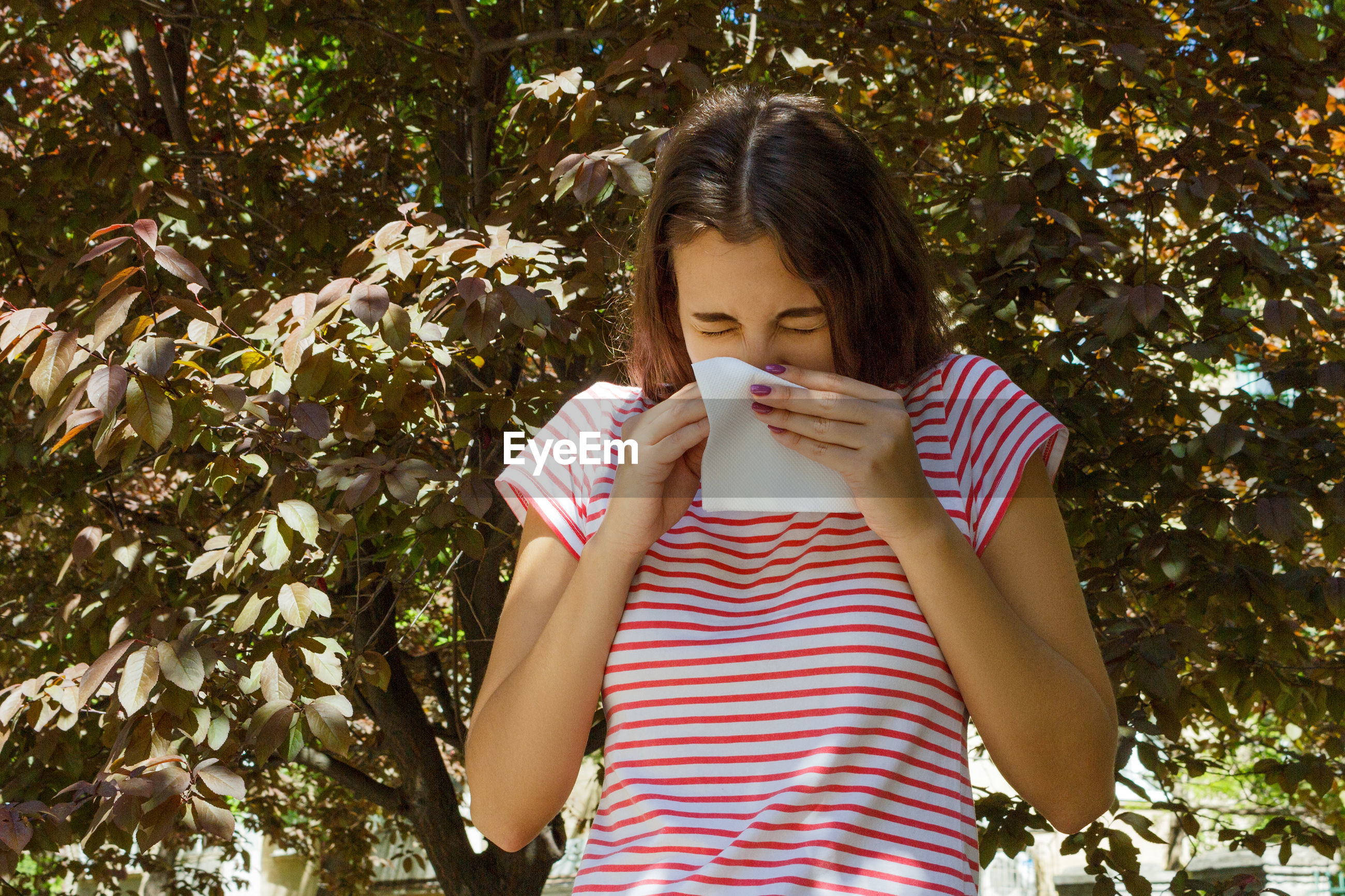 Young woman sneezing while standing against plants in park