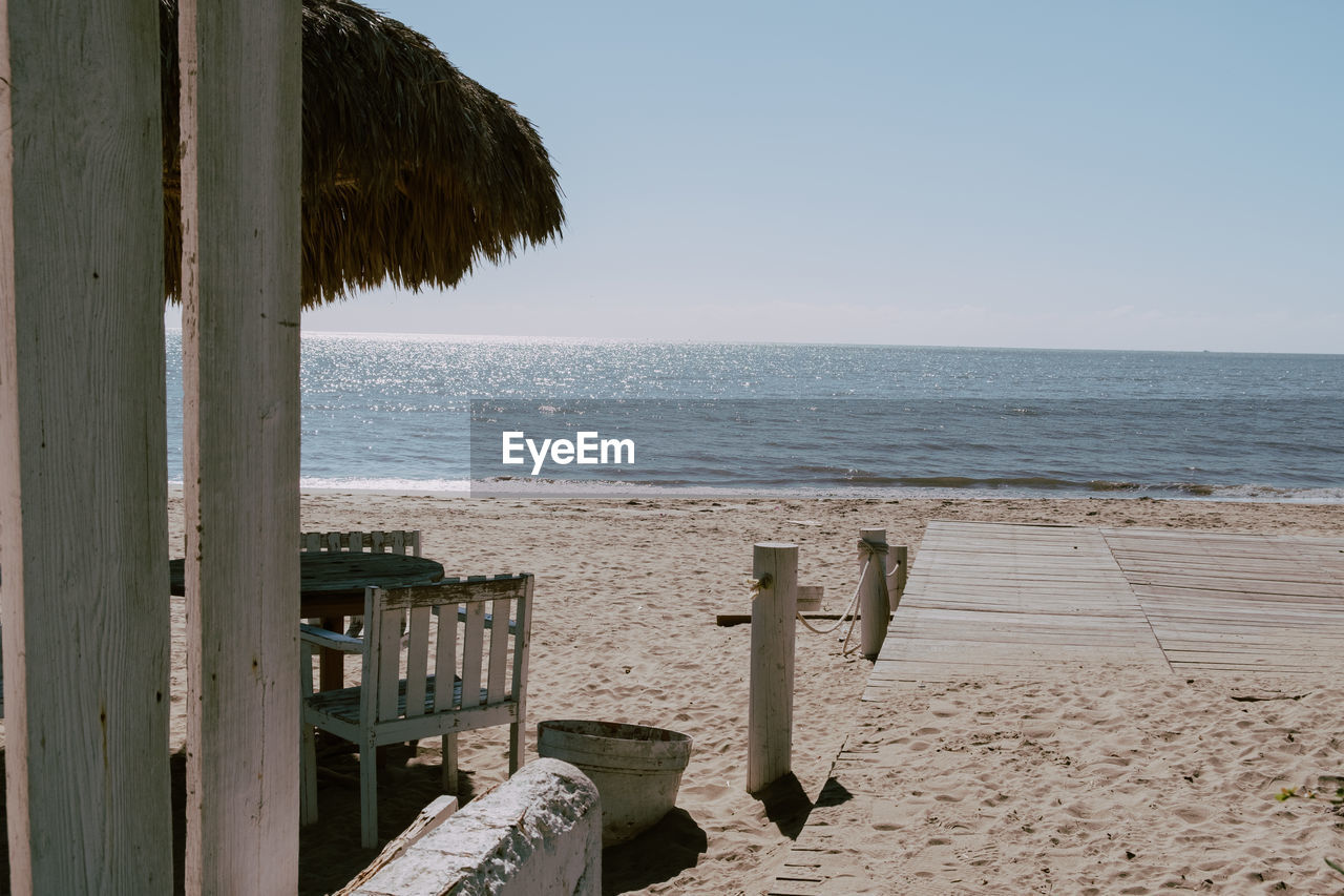 sea, water, beach, land, sky, horizon over water, horizon, sand, tranquility, nature, tranquil scene, scenics - nature, beauty in nature, wood - material, day, no people, outdoors, clear sky, motion, wooden post