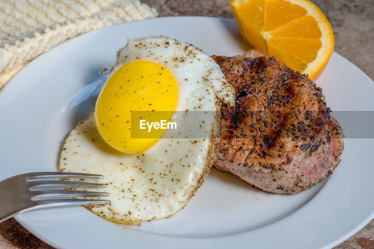 food, food and drink, ready-to-eat, plate, healthy eating, freshness, indoors, wellbeing, still life, fork, kitchen utensil, egg, meal, eating utensil, serving size, table, no people, high angle view, close-up, fruit, fried, egg yolk, breakfast, fried egg, temptation, snack