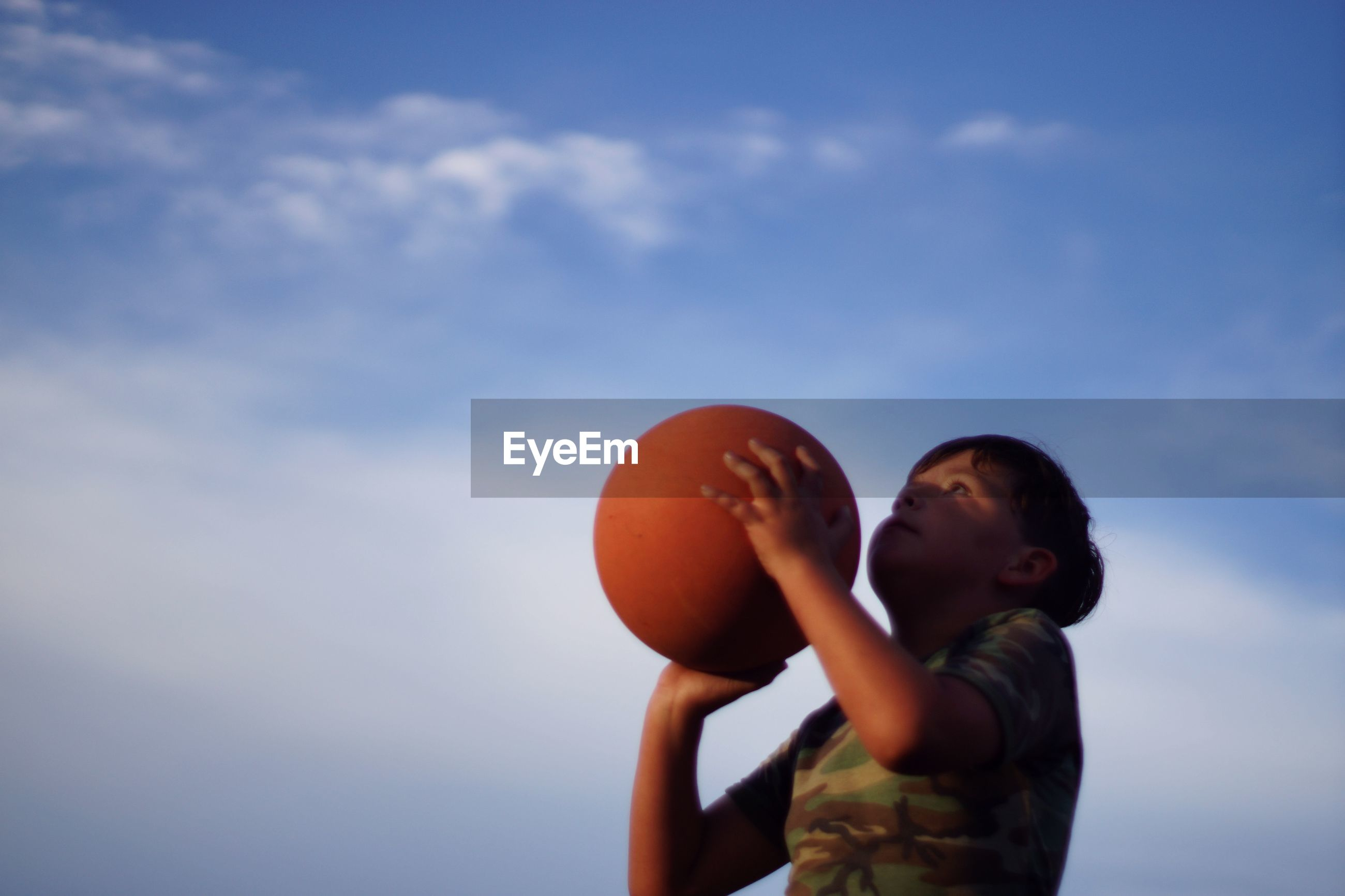 Low angle view of boy playing with basketball against sky