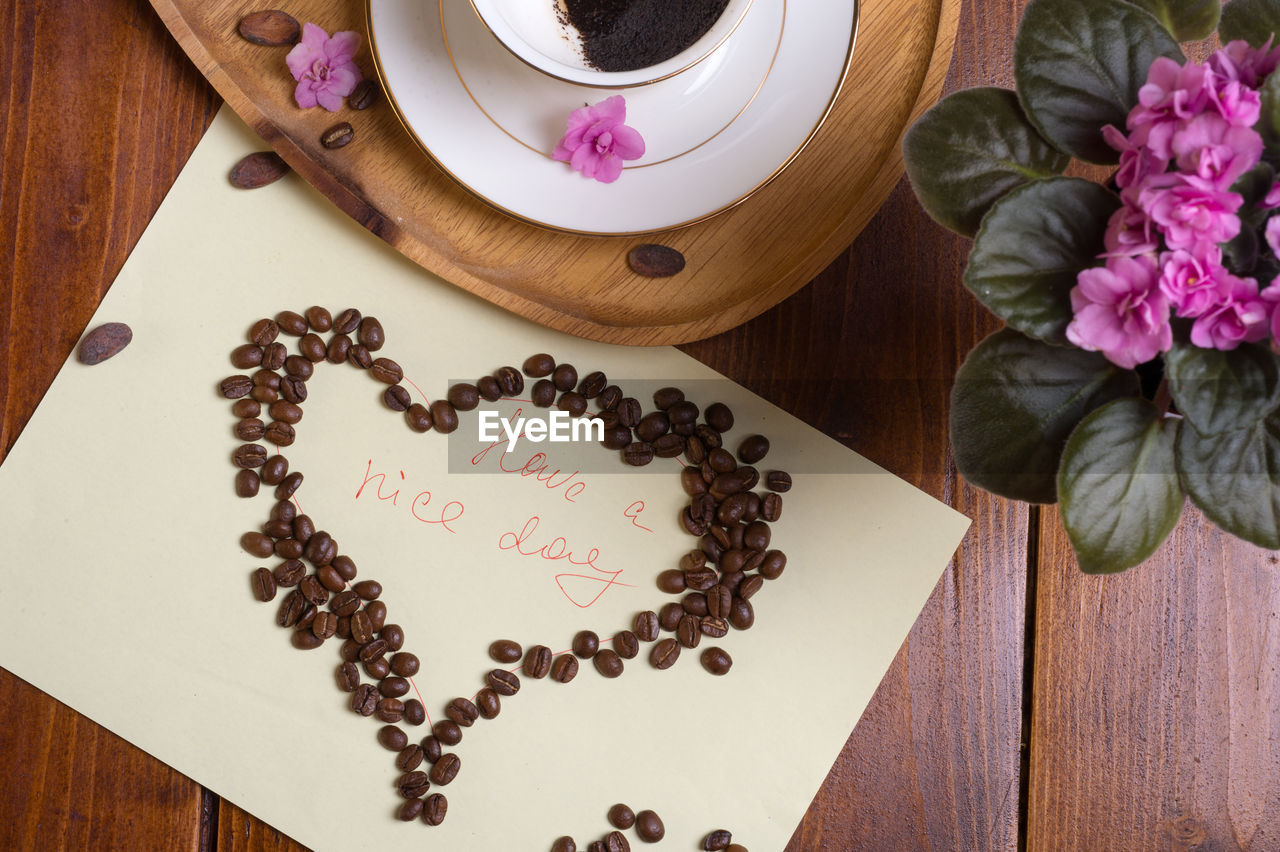 food and drink, flower, table, flowering plant, freshness, food, coffee - drink, baked, high angle view, text, coffee cup, cup, coffee, indoors, sweet food, mug, drink, plant, western script, wood - material, no people, temptation, crockery, flower head