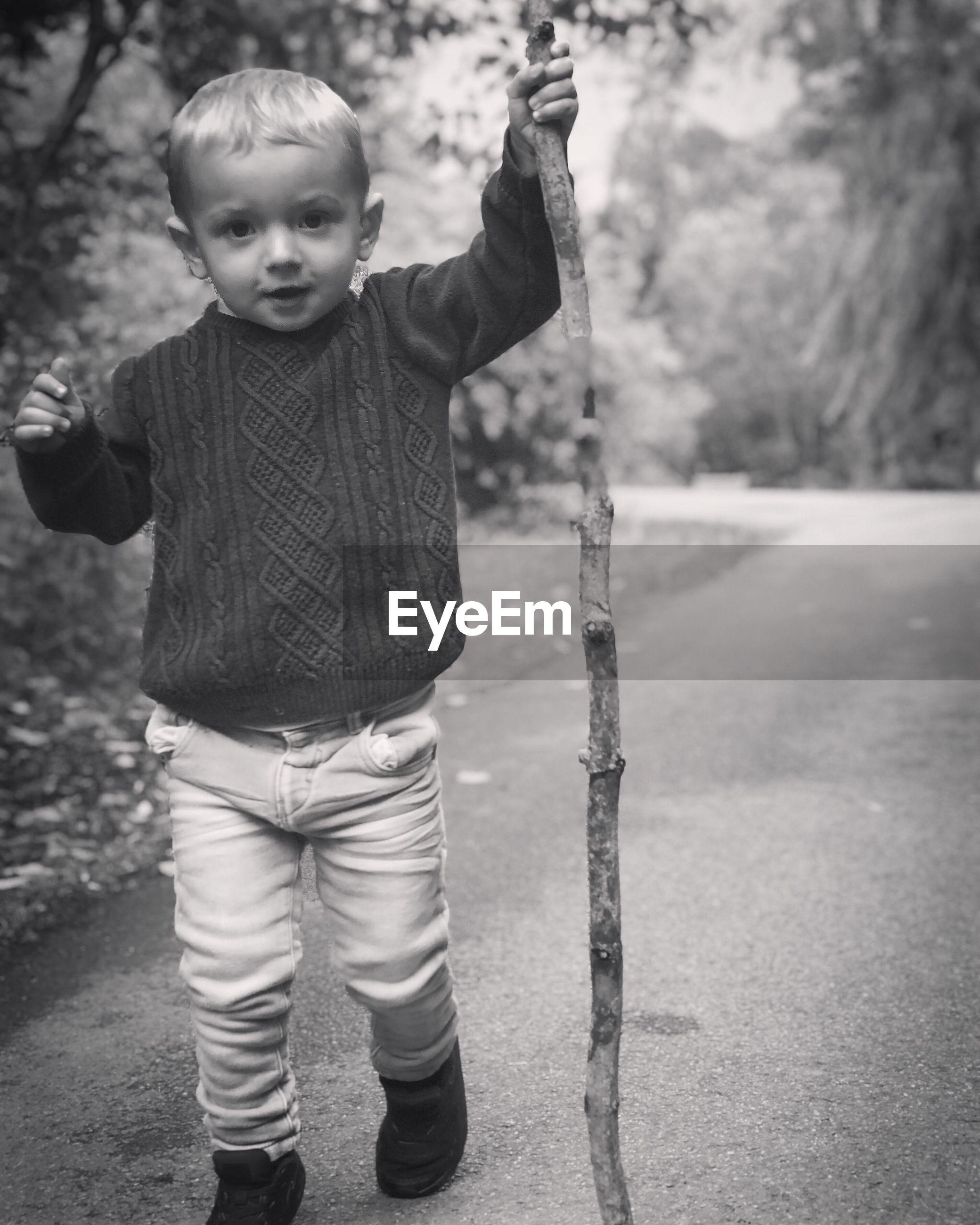 Portrait of cute boy with stick walking on road