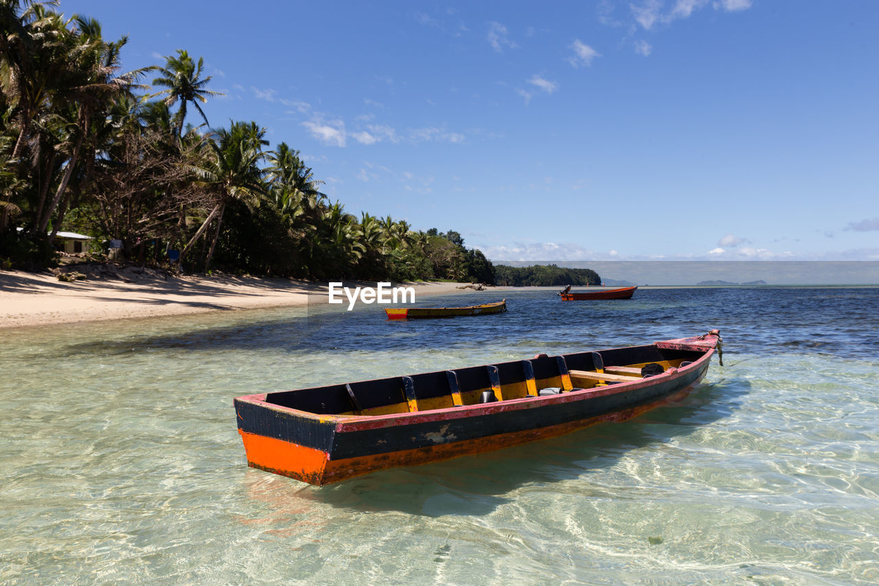 nautical vessel, water, transportation, mode of transportation, sea, tree, sky, waterfront, plant, nature, palm tree, beauty in nature, tropical climate, day, sunlight, outdoors, scenics - nature, no people, motion, rowboat