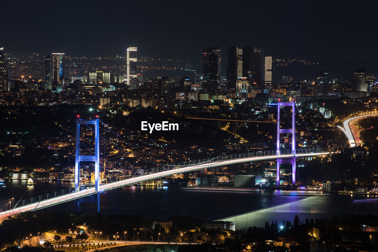Illuminated bosporus bridge and cityscape at night