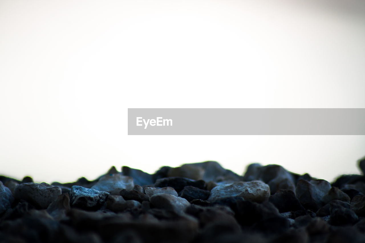 rock - object, no people, clear sky, selective focus, nature, close-up, outdoors, day, beauty in nature, pebble beach, sky, freshness