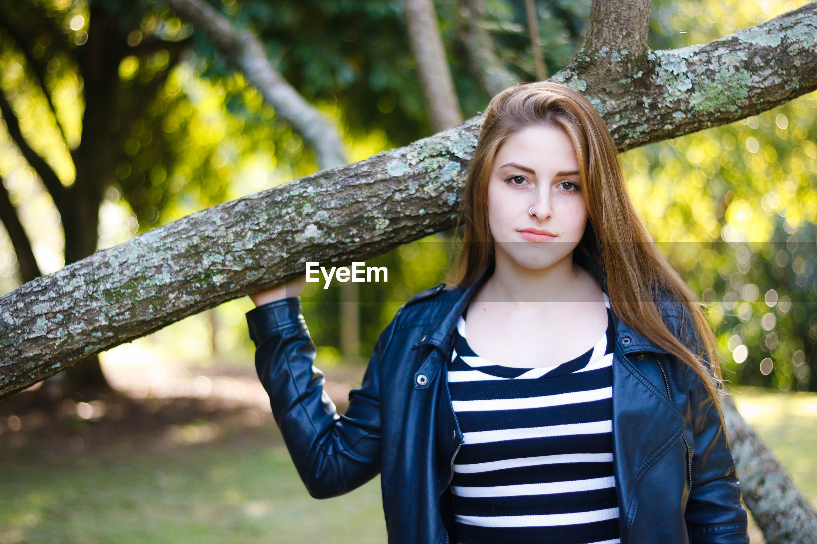 Portrait of woman standing against tree trunk at park