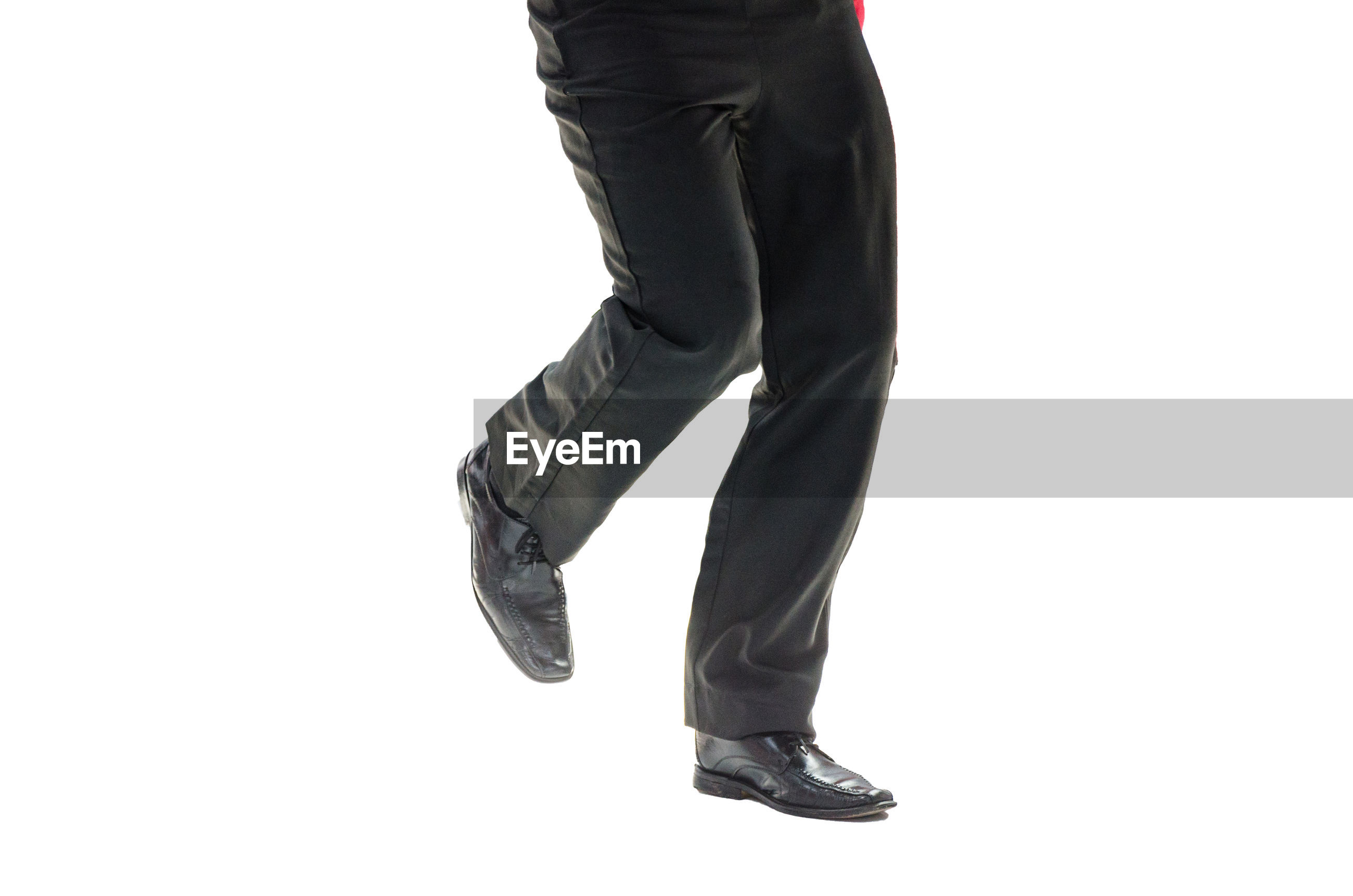 Low section of man standing against white background
