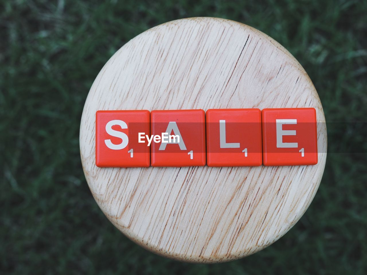 High angle view of sale text on wooden table