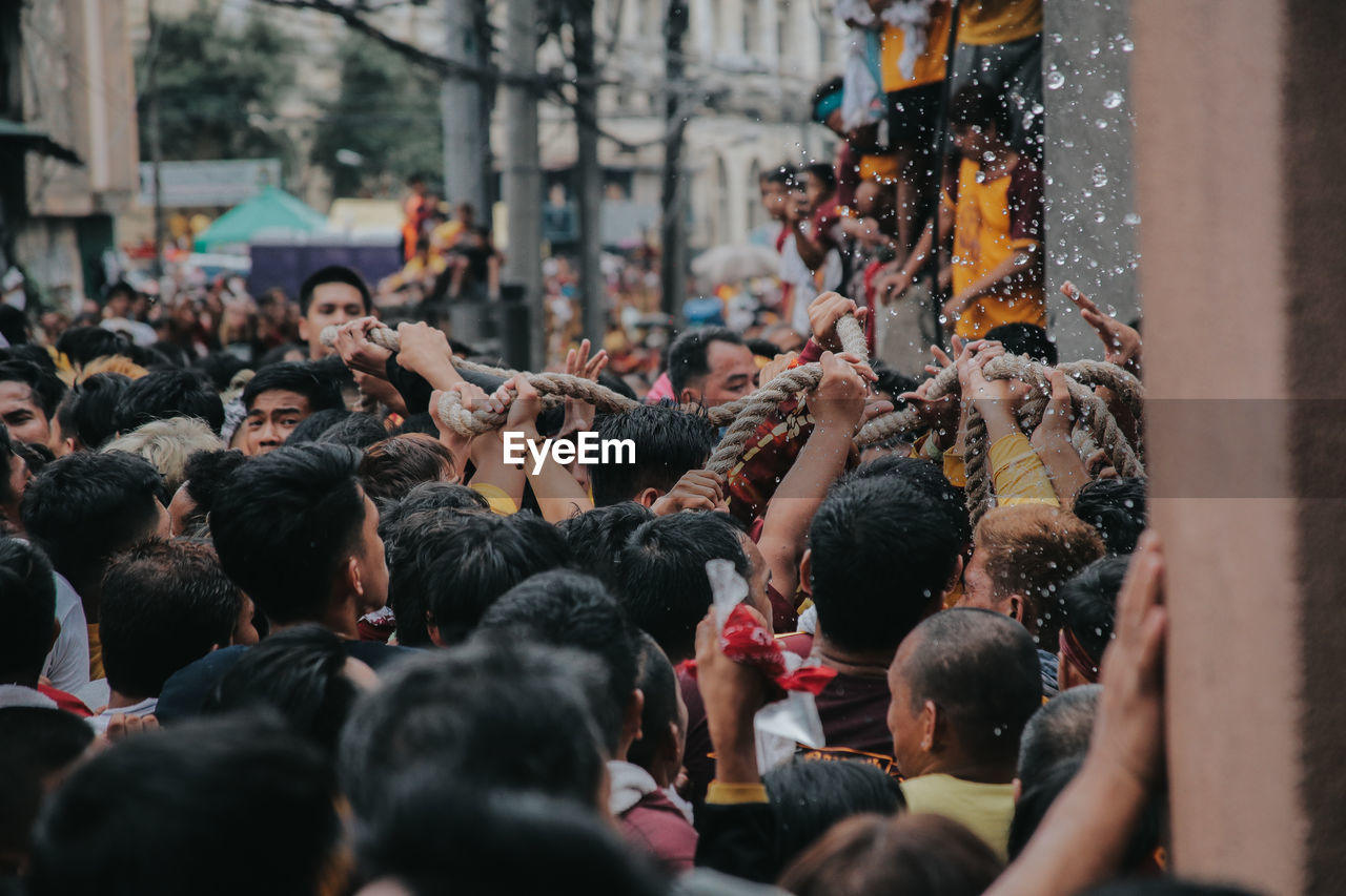 crowd, large group of people, group of people, city, real people, street, architecture, women, built structure, adult, human arm, men, lifestyles, day, arms raised, building exterior, togetherness, event, selective focus, outdoors, human limb
