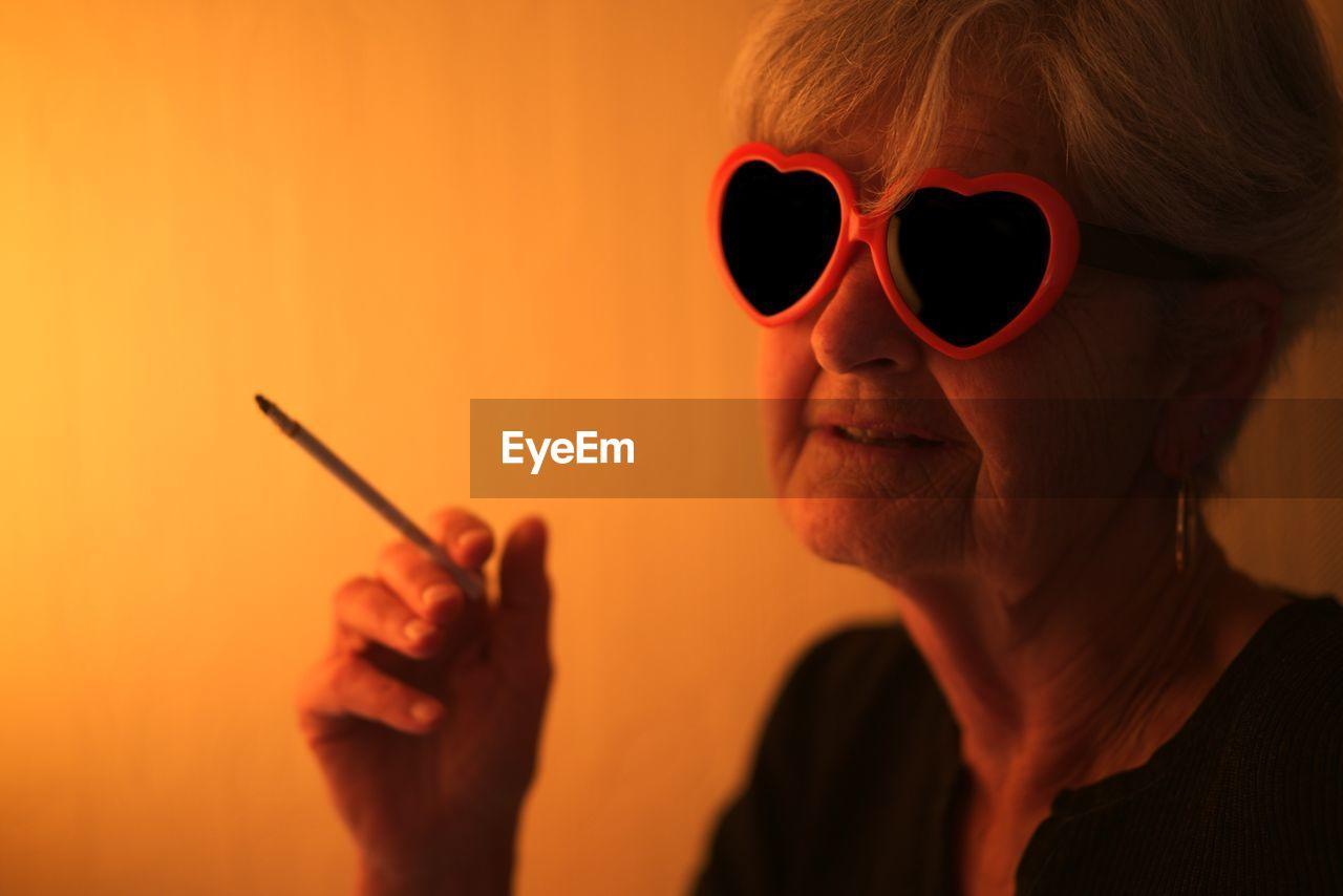 Senior Woman Wearing Heart Shape Sunglasses Smoking Cigarette At Home