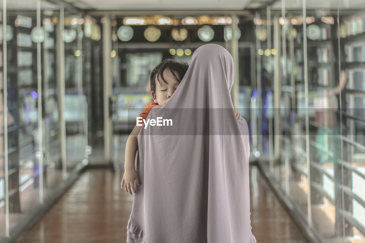 real people, one person, indoors, lifestyles, women, adult, standing, glass - material, rear view, leisure activity, architecture, focus on foreground, hair, three quarter length, clothing, religion, incidental people, young women, waist up, hairstyle