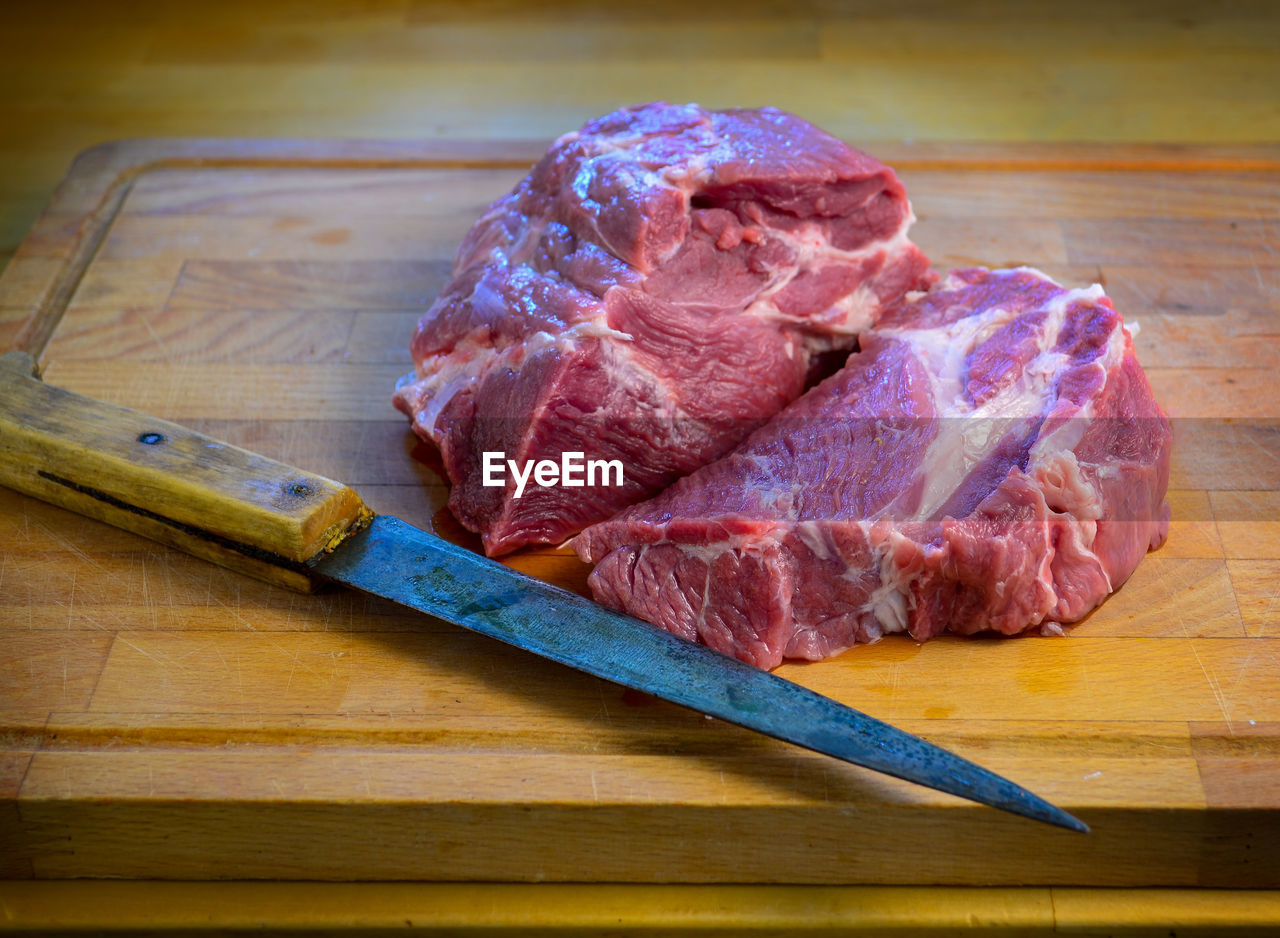 High angle view of meat on cutting board next to knife