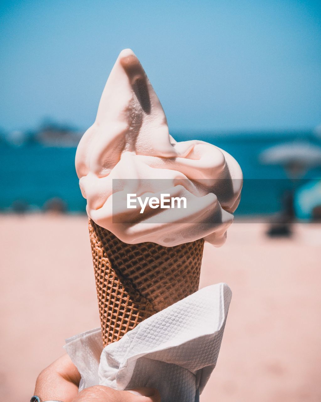 Cropped Hand Of Woman Holding Ice Cream Cone At Beach Against Clear Blue Sky