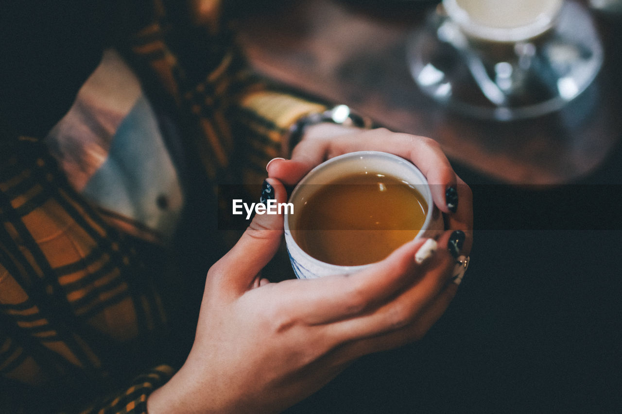 food and drink, holding, cup, drink, refreshment, real people, mug, indoors, human hand, one person, lifestyles, tea, hand, hot drink, focus on foreground, close-up, tea - hot drink, human body part, coffee, freshness, tea cup, drinking, finger