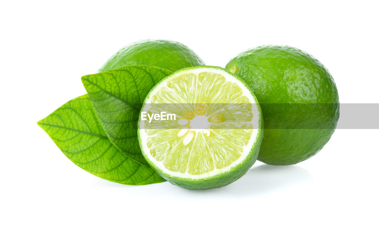 white background, fruit, studio shot, healthy eating, green color, freshness, slice, citrus fruit, food, close-up, food and drink, plant part, cut out, wellbeing, indoors, leaf, still life, no people, cross section, lemon, ripe