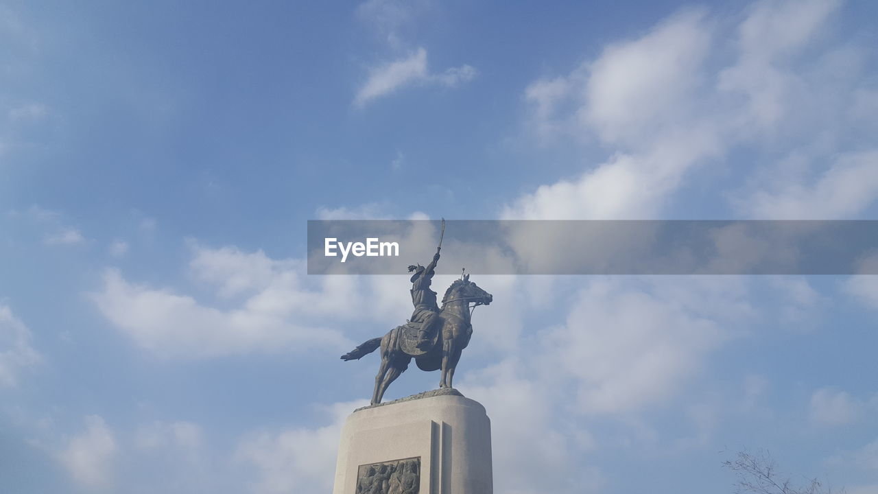 cloud - sky, sky, representation, sculpture, low angle view, art and craft, statue, human representation, creativity, architecture, nature, male likeness, livestock, day, the past, no people, history, craft, outdoors