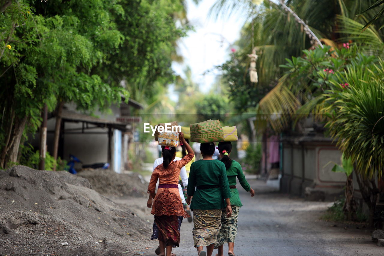 Women With Baskets Walking On Road Amidst Trees