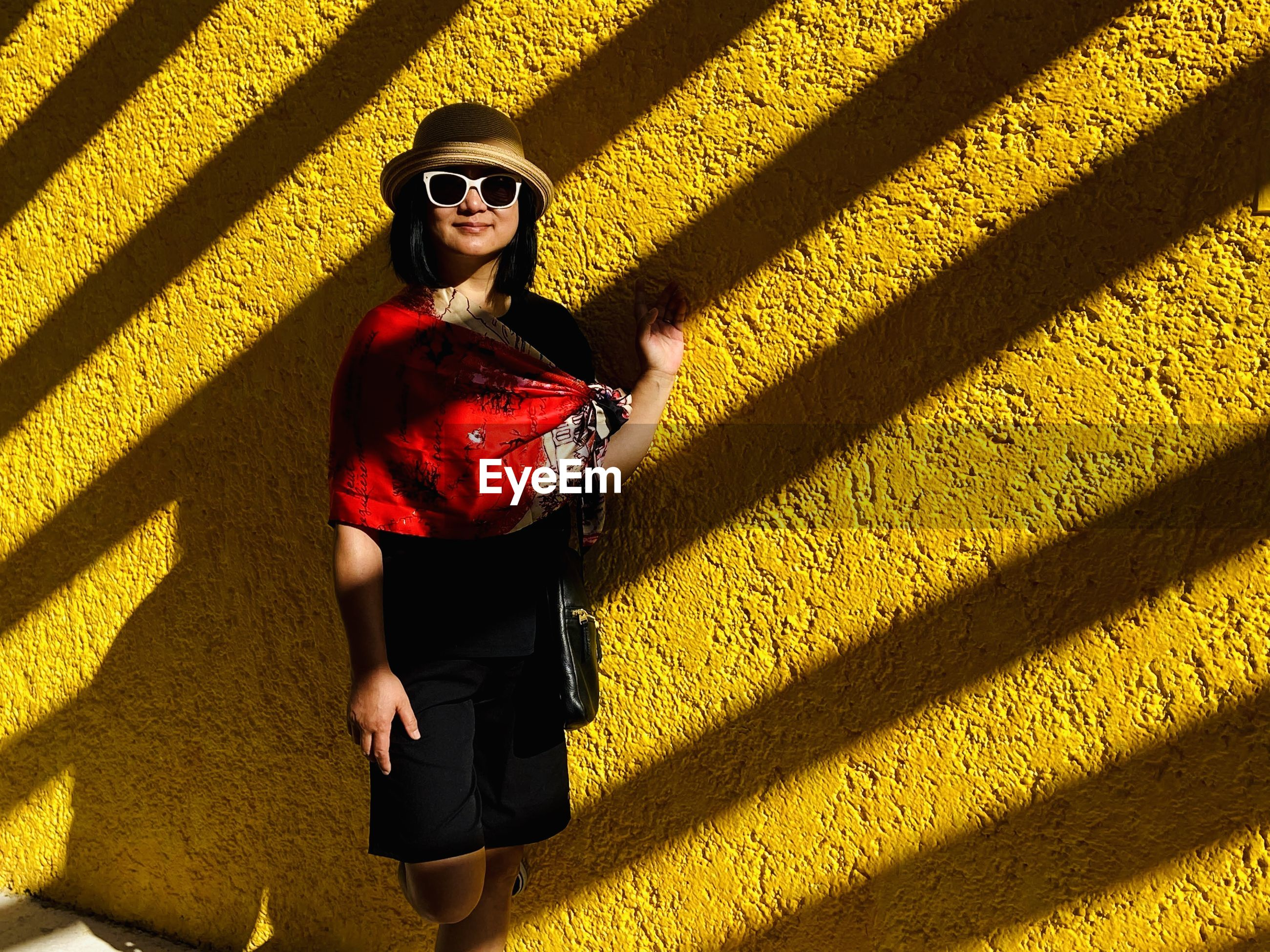 Portrait of woman wearing sunglasses while standing against wall