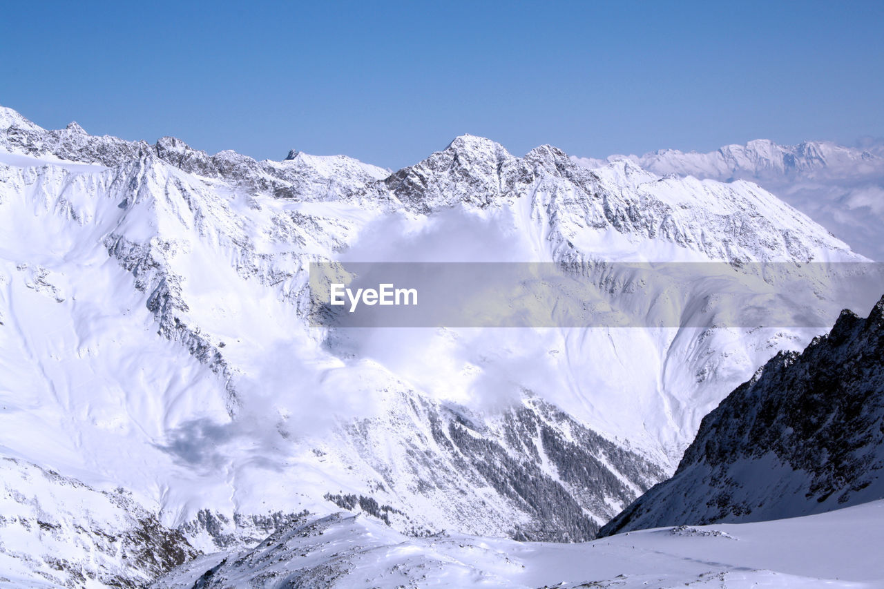cold temperature, mountain, snow, winter, scenics - nature, beauty in nature, sky, snowcapped mountain, environment, landscape, tranquil scene, mountain range, nature, tranquility, no people, non-urban scene, mountain peak, day, blue, formation