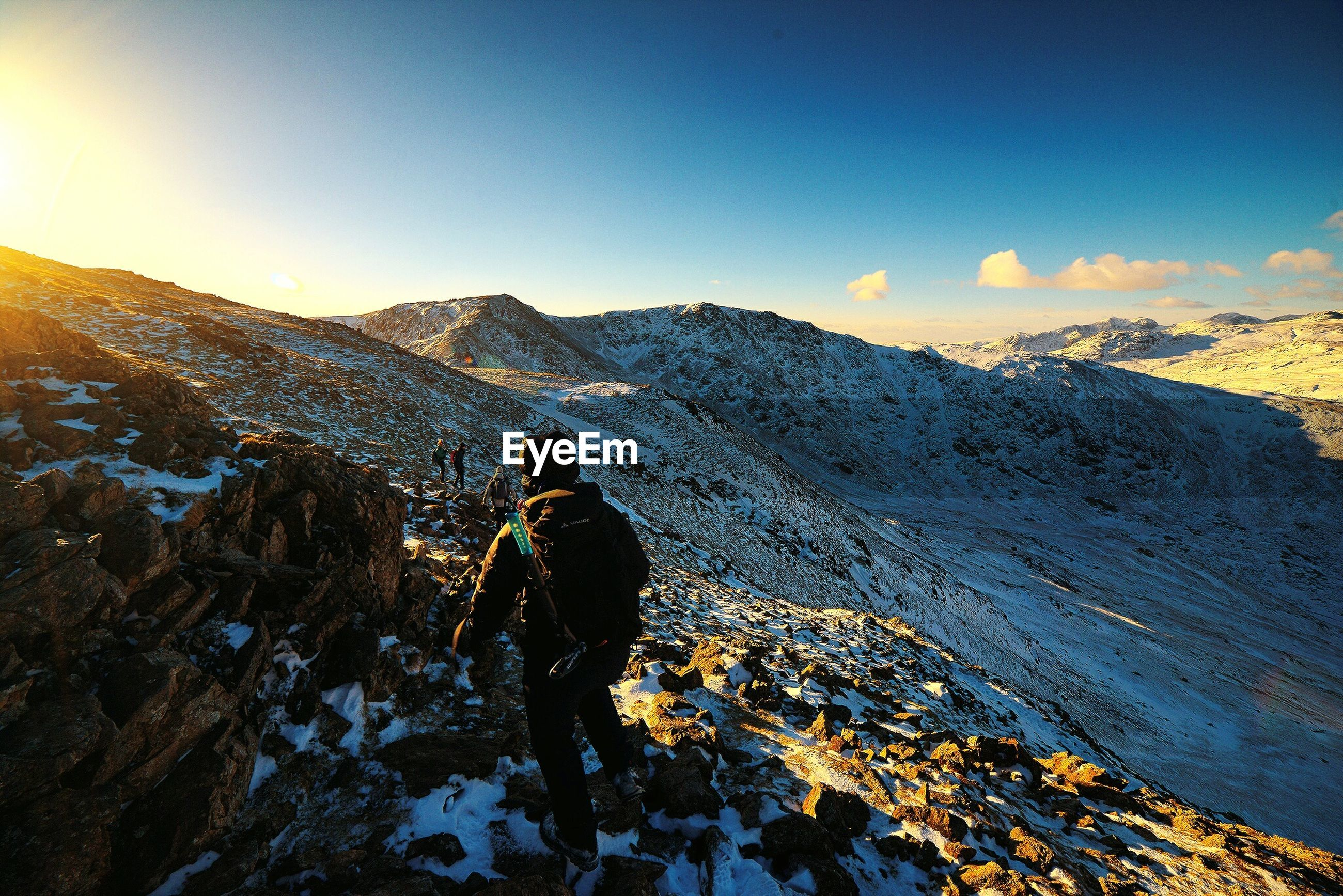 Full length rear view of man standing on snow covered mountains against sky