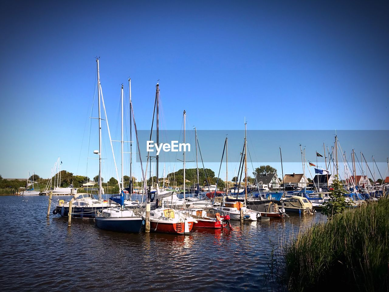 nautical vessel, transportation, mode of transportation, water, moored, sailboat, sky, mast, clear sky, waterfront, harbor, pole, nature, day, no people, blue, reflection, river, copy space, outdoors, yacht, marina, port, anchored
