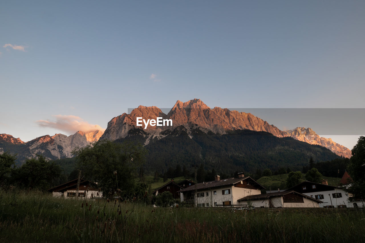 HOUSES BY BUILDINGS AGAINST MOUNTAINS