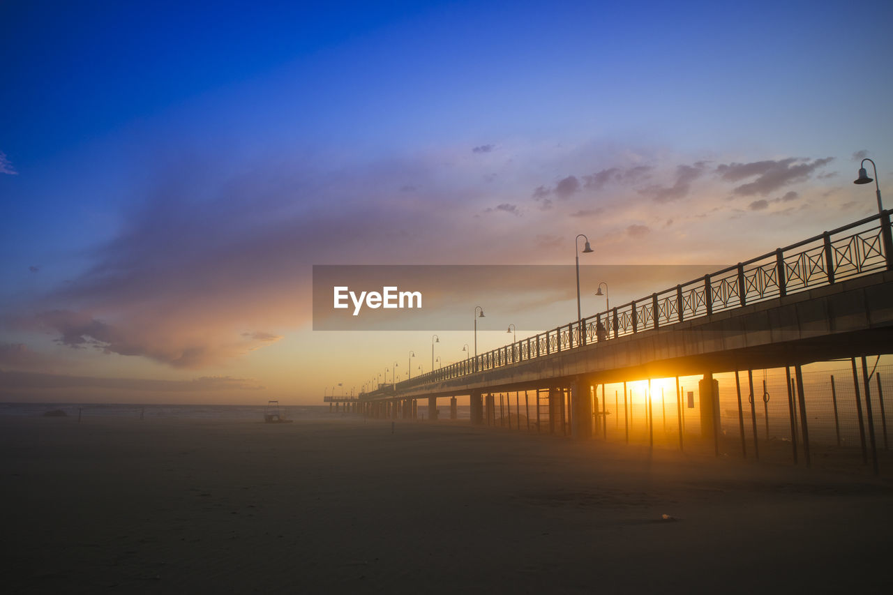 sky, sunset, water, built structure, architecture, sea, beauty in nature, cloud - sky, scenics - nature, bridge, connection, bridge - man made structure, orange color, nature, no people, tranquil scene, silhouette, beach, outdoors