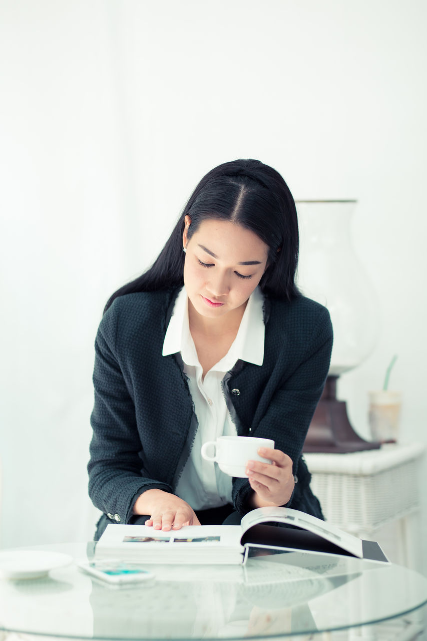 Businesswoman reading book at table