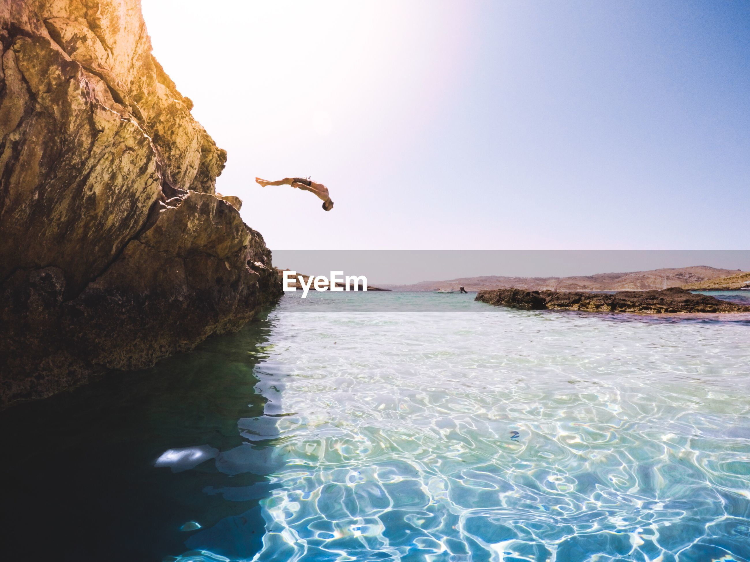 Man diving into sea from cliff against clear sky