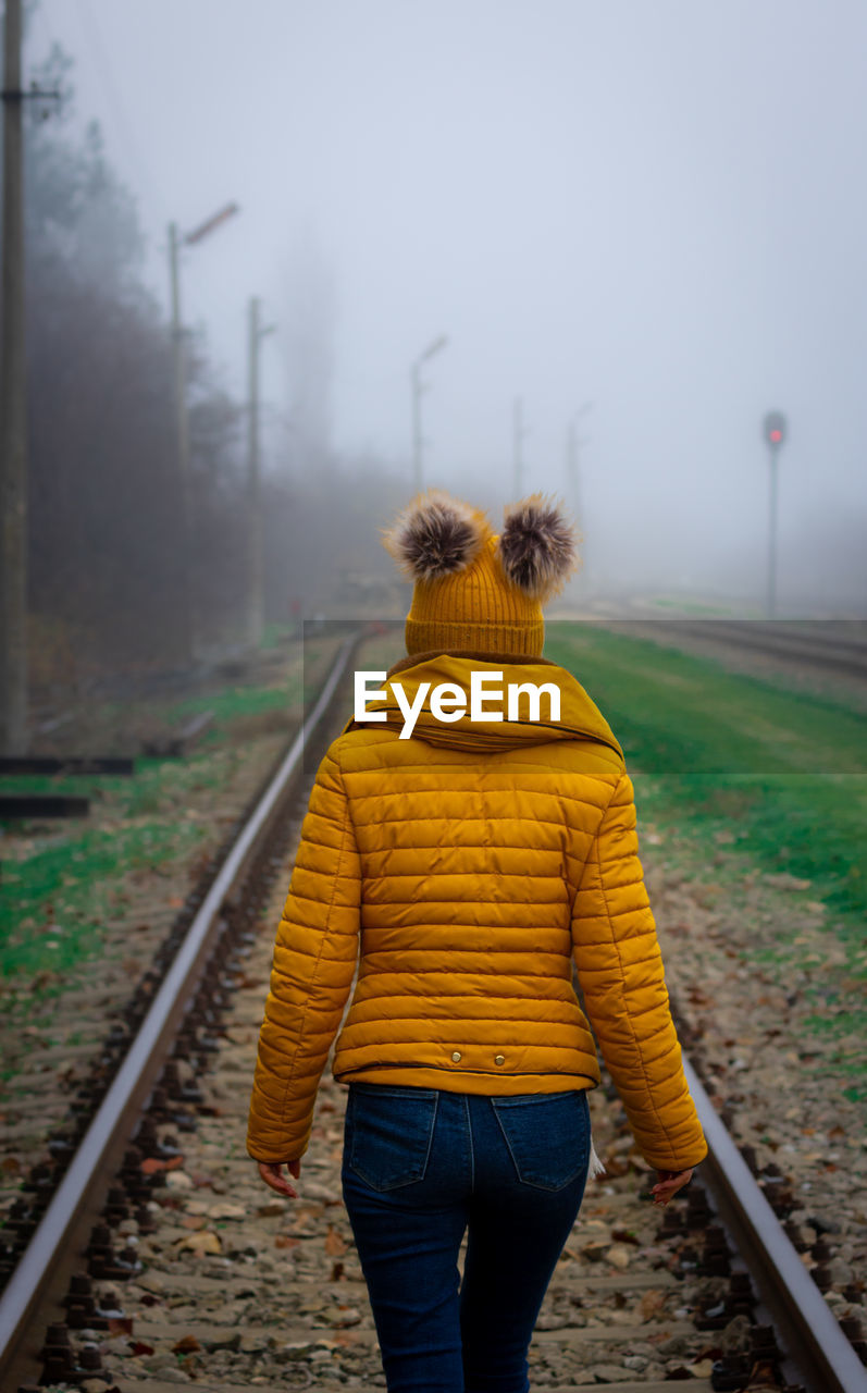 REAR VIEW OF PERSON ON RAILROAD TRACK