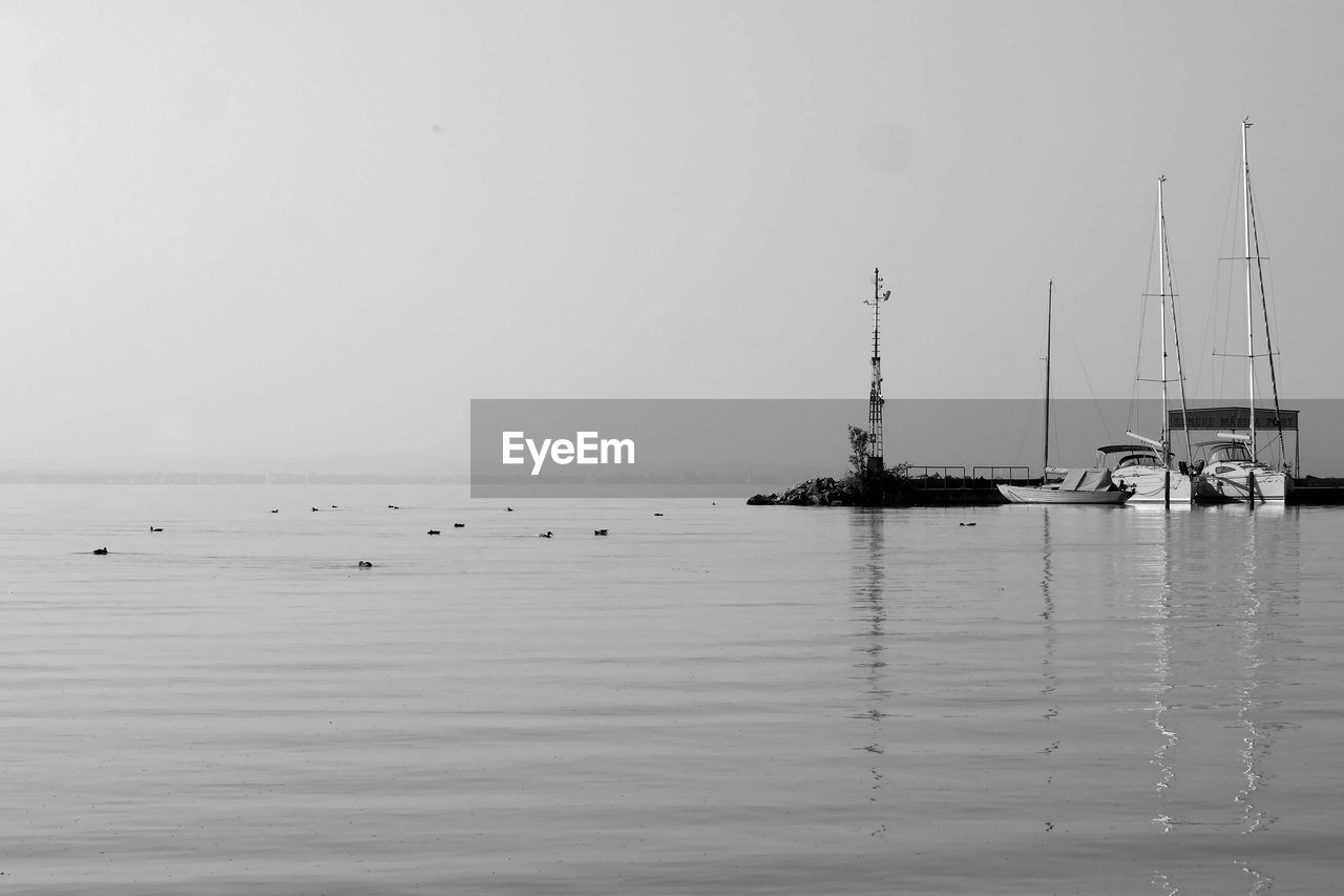 water, nautical vessel, transportation, sea, mode of transportation, waterfront, sky, horizon, horizon over water, tranquility, scenics - nature, tranquil scene, no people, beauty in nature, nature, sailboat, clear sky, copy space, day, outdoors, yacht, fishing industry, fishing boat, marina