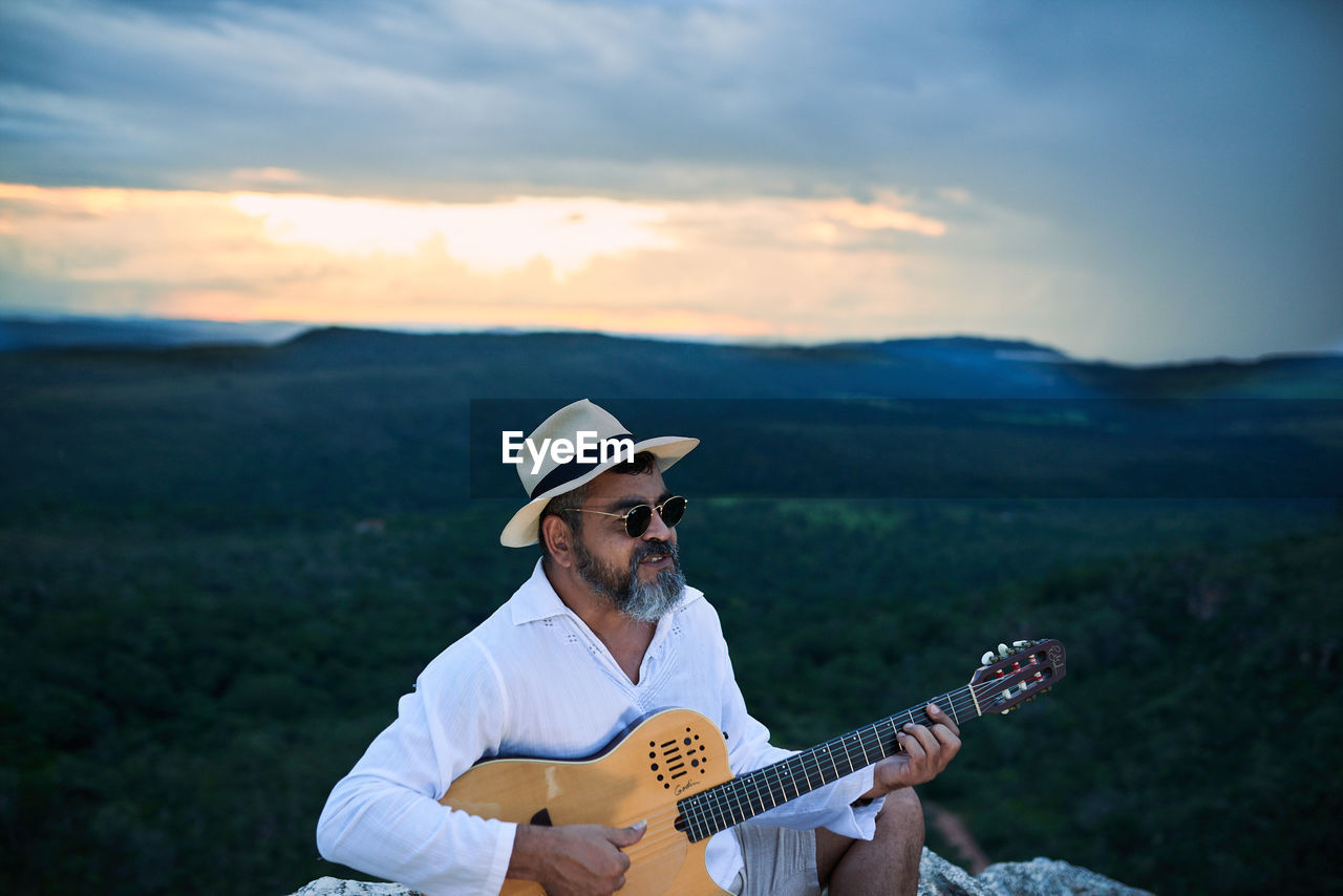 Man playing guitar on mountain against sky during sunset
