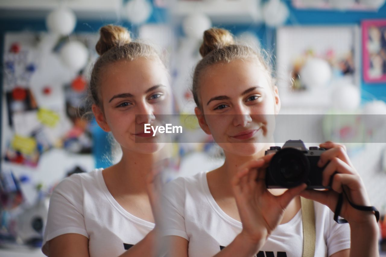 Reflection of smiling young woman with camera seen in mirror at home
